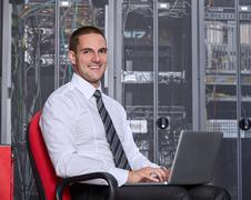Young man sitting in a modern datacenter server room - stock photo