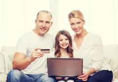 Parents and girl with laptop and credit card Stock Photos