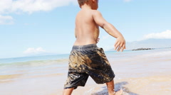 Black toddler playing in the ocean - stock footage