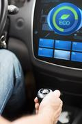 Hand with gearshift and car eco mode on screen Stock Photos