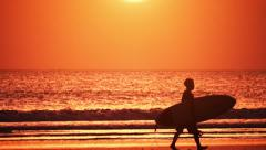 Sport lifestyle background of surfer with board walking along beach at sunset - stock footage