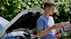 Man checking manual how to fix car problem Stock Footage