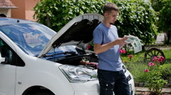 Man looking through car manual outside Stock Footage