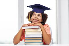 happy african bachelor girl with books at home - stock photo