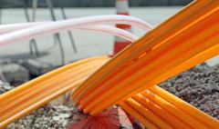 Orange pipes for fiber optics in a large city road construction - stock photo