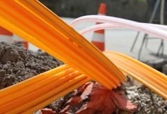 Orange pipes for fiber optics in a large city road construction site Stock Photos