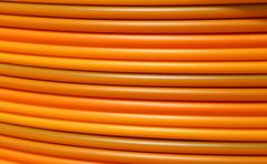 coils of orange plastic pipes for the installation of underground utilities - stock photo