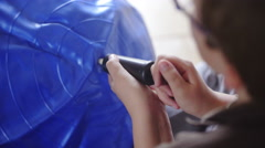 Over shoulder view of inflating blue ball 4K - stock footage