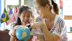 Little Asian student looking at globe while listening to teacher - stock footage