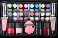 Stock Photo of Make up case containing colorful eyeshadows, lipsticks, lip glos