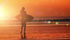 Male surfer walks on beach caring surfboard at hot orange sunset with sunlight - stock footage