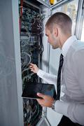 Man solving a problem with wires in a modern datacenter server room - stock photo