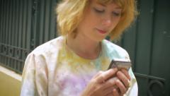 Handheld shot of young blond woman walking and texting on a cell phone Arkistovideo
