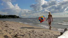 beautiful girl with colorful balloons walking on the beach - stock footage