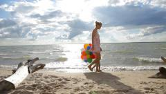 Woman with little child holding colorful balloons goes along the coast Stock Footage