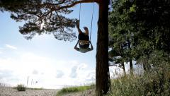 Boy swinging on a swing under a high pine tree Stock Footage