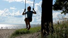 Young boy sway on swing on the beach Stock Footage