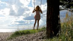 Girl is having fun on a swing underneath a tree on the beach. Stock Footage