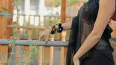 Feminine girl in the clothes for oriental dance walks in the garden and smelling Stock Footage