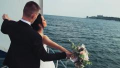 Newlyweds stand on a bow of a sailing yacht like in titanik slow motion Stock Footage