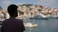 Silhouette of a man with glasses who looks to the island Stock Footage