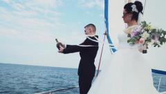 the groom opens a bottle of champagne on a bow of a sailing yacht slow mot - stock footage