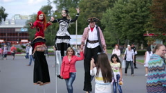 Show of street performers circus. Pedestrians photographed with actors on stilts Stock Footage
