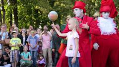 Show of street performers circus. Clown-juggler performs in front of children. Stock Footage
