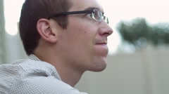 Man with glasses staring off angrily - stock footage