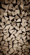 Neatly stacked wood as background, vertical - stock photo