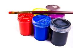 Bottles with gouache paints and brushes for artistic paintings. - stock photo