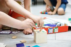 Children playing with homemade educational toys - stock photo