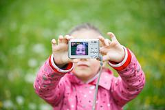 Little girl making a selfie with digital camera Stock Photos