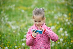 Girl watching cartoon and playing games on smart phone Stock Photos