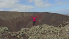 Stock Video Footage of AERIAL: Young woman raising arms on top of volcano crater
