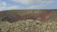 Stock Video Footage of AERIAL: Flying around woman standing on top of volcano crater