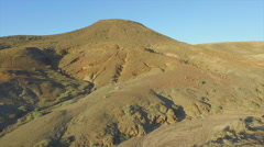 AERIAL: Flying up and over woman on top of volcano - stock footage