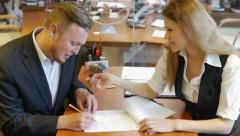 Businessman sitting in the office with a woman signs documents Stock Footage