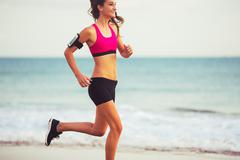 Sports Fitness Woman Running on the Beach at Sunset Stock Photos