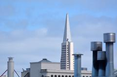 Transamerica Pyramid against house chimney's and roof tops San Francisco, CA. Stock Photos
