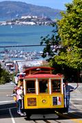 Passengers riding on Cable Car No. 15 with Alcatraz Island in the background Kuvituskuvat