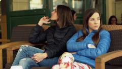 Two offended female friends sitting in cafe in city HD - stock footage