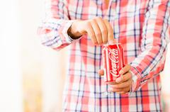 Closeup of young man hands opening a Coca-Cola can - stock photo