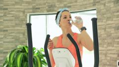 Young woman exercising on elliptical machine in the gym and drinking water Stock Footage