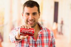 Attractive young man smiling holding a Coca-Cola can Stock Photos