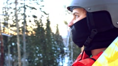 Man in a helmet riding a mountain on a lift with a snowboard on a background of Stock Footage