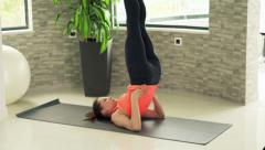 Young, pretty woman exercising, doing shoulder stand on mat in gym - stock footage