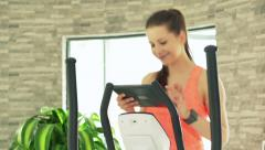 Young woman with tablet computer exercising on elliptical machine in gym Stock Footage