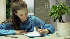 Young female student drawing project sitting by table at home Stock Footage