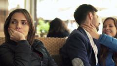 Young, jealous woman sitting next to happy couple in love  Stock Footage